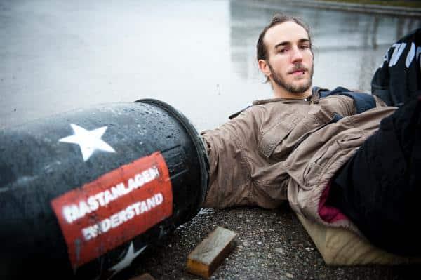 Ein, an ein Betonfass angeketteter Aktivist in einer Seitenzufahrt. Foto: cg/ visual-rebellion.com