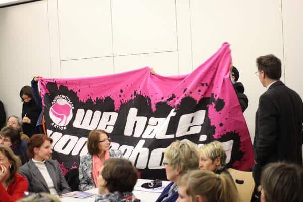 Tumultartige Szenen: Aktivistinnen entrollen ein Transparent im Pfarrheim. Albertin geht dazwischen. Foto: Roth