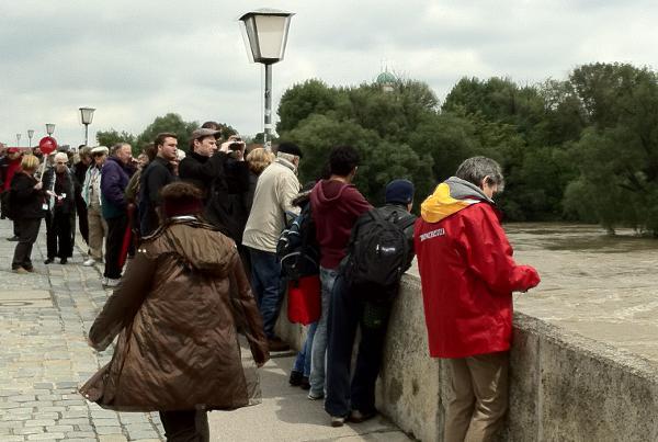 Die Sonne kommt raus und Hochwasser-Touristen drängeln sich auf der Steinernen Brücke.