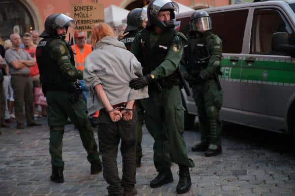 """Der 22jährige wird wie ein Schwerverbrecher abgeführt, dann mit einem """"Verpiss Dich"""" des Platzes verwiesen. Foto: Herbert Baumgärtner"""