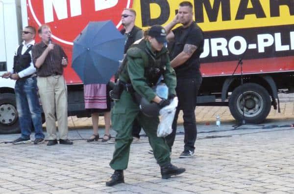 Beweissicherung: Eine Polizeibeamtin sammelt Scherben einer Flasche ein, die während der NPD-Kundgebung flog. Foto: as