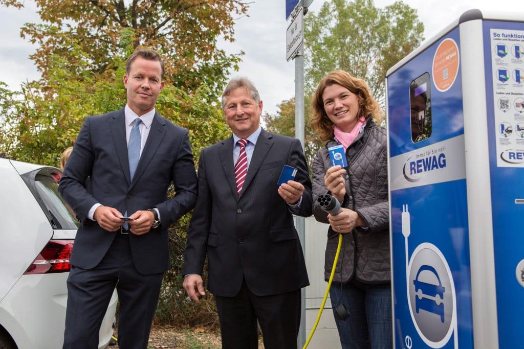 Der REWAG-Vorstandsvorsitzende Olaf Hermes, Bürgermeister Heinz Kiechle und Landrätin Tanja Schweiger bei der Eröffnung der REWAG-Ladesäule in Neutraubling.