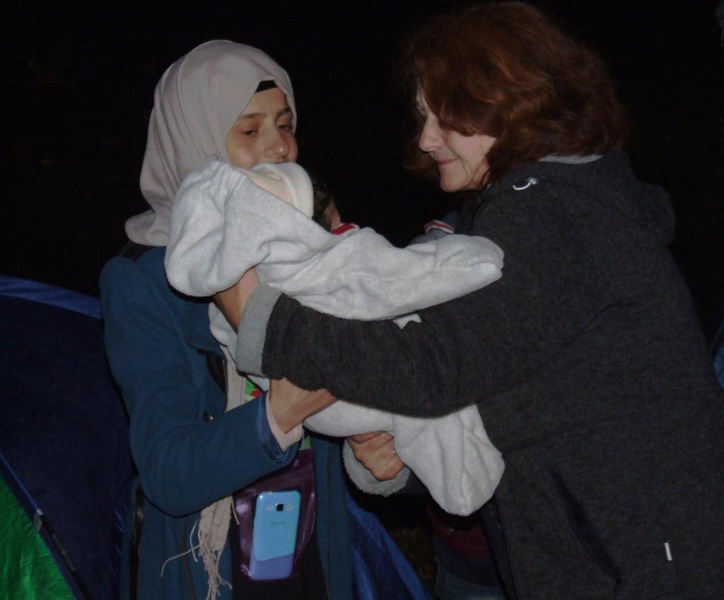 Maria Wagner hilft einer Geflüchteten mit ihrem Baby.