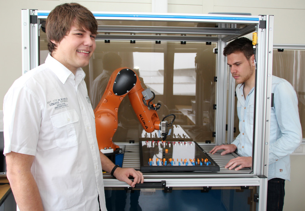 Markus Reichl (links) und Markus Webert, beides Informatik-Studierende der OTH Regensburg, lassen einen Roboter das Brettspiel Siedler von Catan spielen. Foto: OTH Regensburg