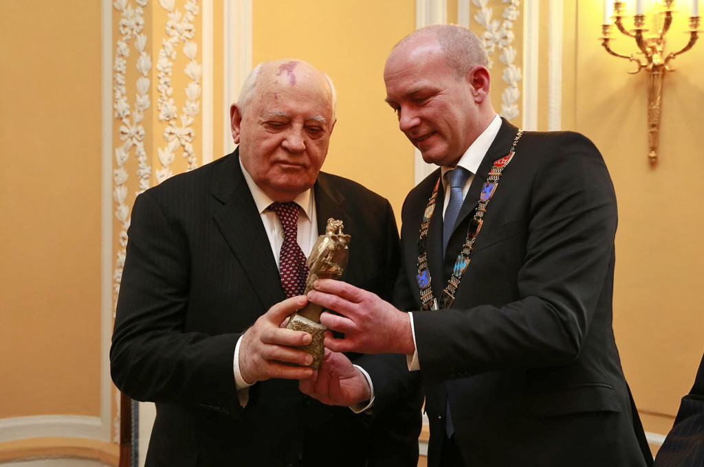 """Interessiert betrachtet Michail Gorbatschow den """"doppelten Nepomuk"""" – eine kleine Bronzestatue, die gemeinsam mit dem Brückenpreis vergeben wird. Bildnachweis: Stadt Regensburg/Stefan Effenhauser"""