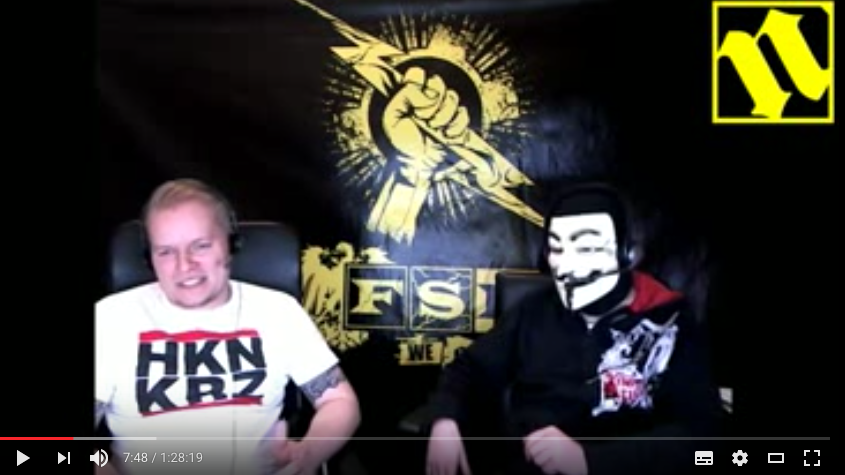 """Im Studio von FSN-TV: Schröder (links) mit modischer Botschaft. Das entsprechende Symbol wäre verboten, das Akronym """"HKN KRZ"""" ist es nicht. Foto: Screenshot Youtube"""