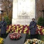 Dekoration beim Volkstrauertag: Blumen, Kränze, Feuerschalen, behelmte und bewaffnete Soldaten