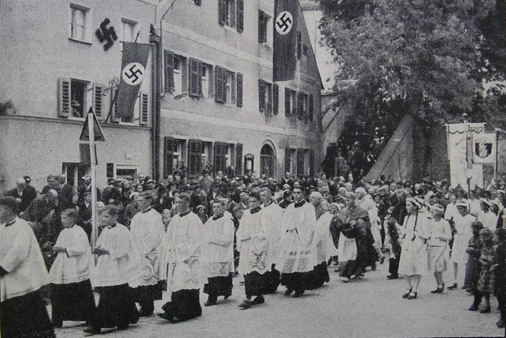 """1937: Ein Jahr später feierte man in Deggendorf """"600 Jahre Gnadenzeit"""" und Bischof Buchberger schritt mit einer feierlichen Prozession durch ein Meer von Hakenkreuzfahnen."""