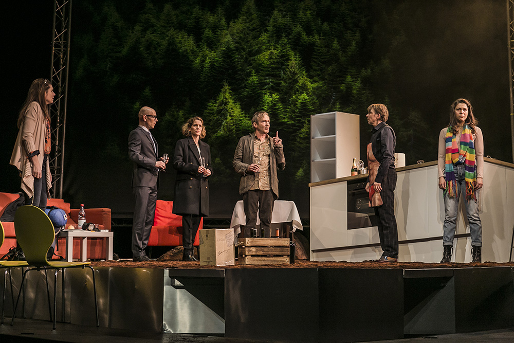 """IKEA Möbel auf Erde: Die Bühne von """"Ein großer Aufbruch"""" droht in den Zuschauerraum zu kippen. Foto: Jochen Quast / Theater Regensburg."""